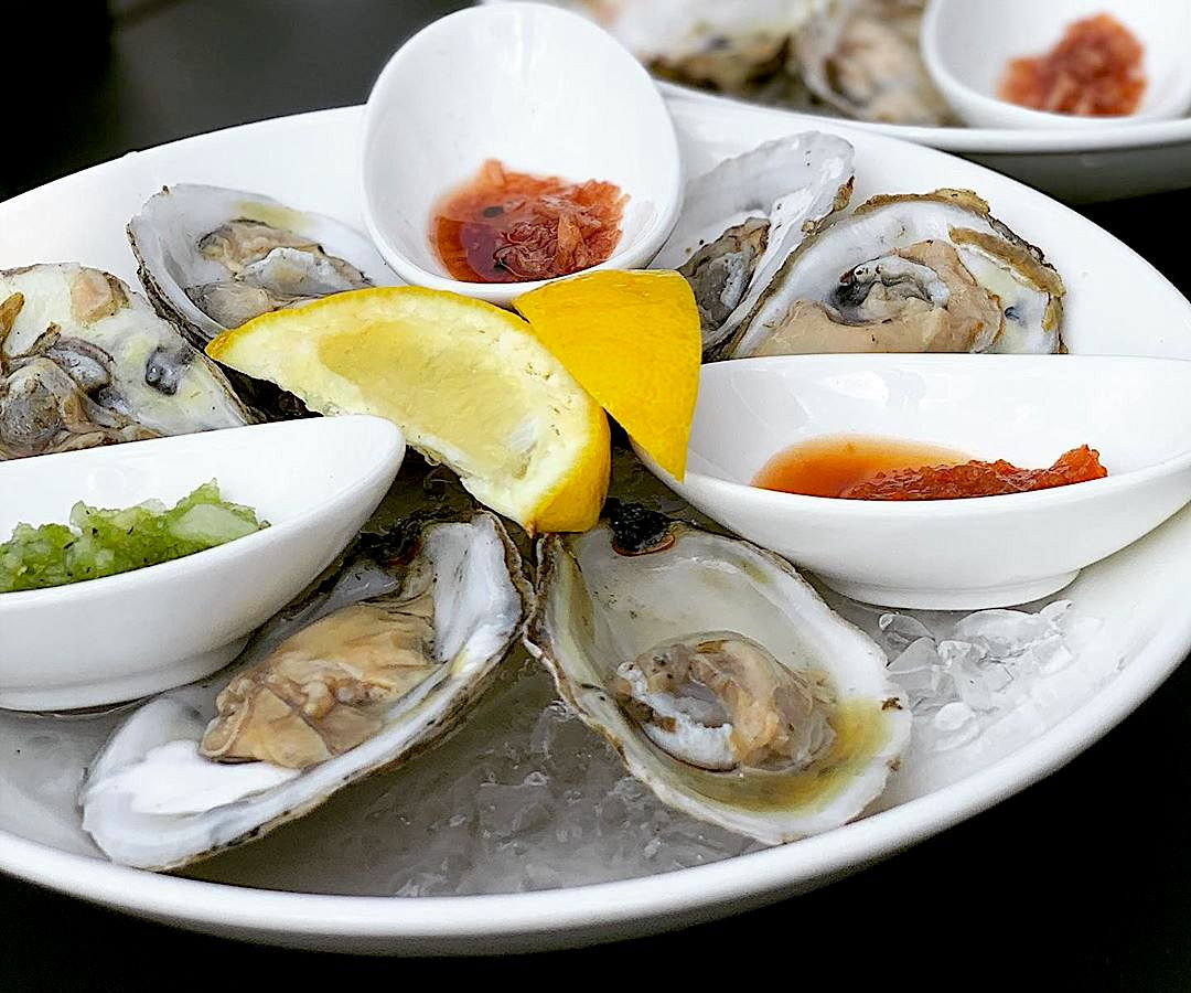 A round tray filled with ice and raw oysters on the half shell.