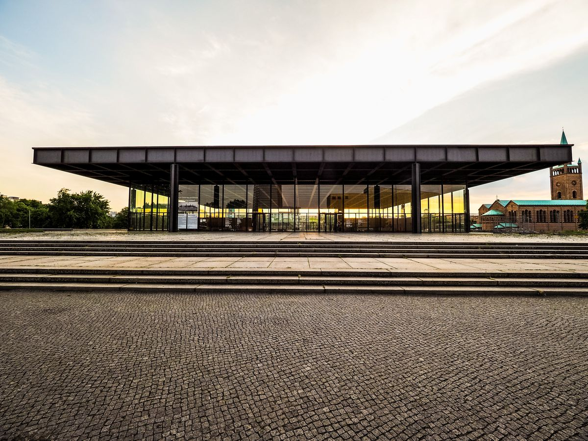 The exterior of the Neue Nationalgalerie in Germany. The steel roof is flat. The building's walls are floor to ceiling windows.