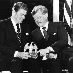 U.S. Sen. Edward Kennedy, D-Mass., right, talks with President Ronald Reagan on June 24, 1985, as they look over an American eagle that graced President John F. Kennedy's desk during a fundraising event for the John F. Kennedy Memorial Library at McLean, Va. Kennedy, the liberal lion of the Senate, died Tuesday after battling a brain tumor. He was 77.