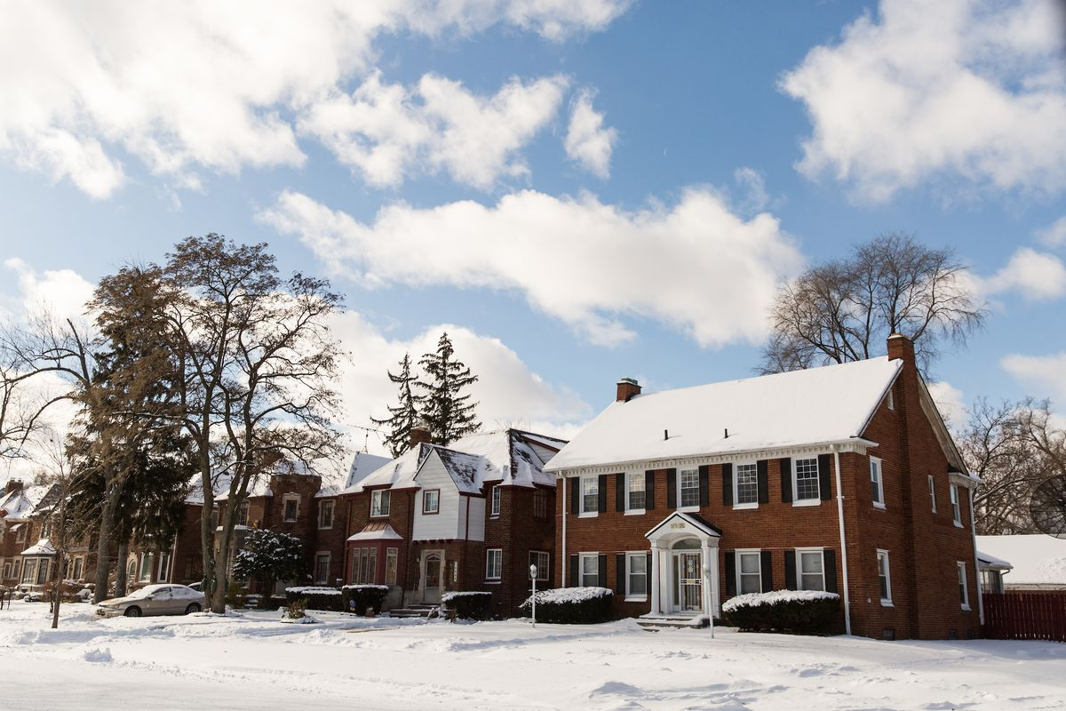 A row of homes on a winter day. There's snow covering the roofs, sidewalks, and roads.