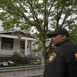 A sheriff deputy stands outside a house where three women escaped Tuesday, May 7, 2013, in Cleveland. Three women who went missing separately about a decade ago were found in the home Monday just south of downtown and likely had been tied up during years of captivity, said police, who arrested three brothers.