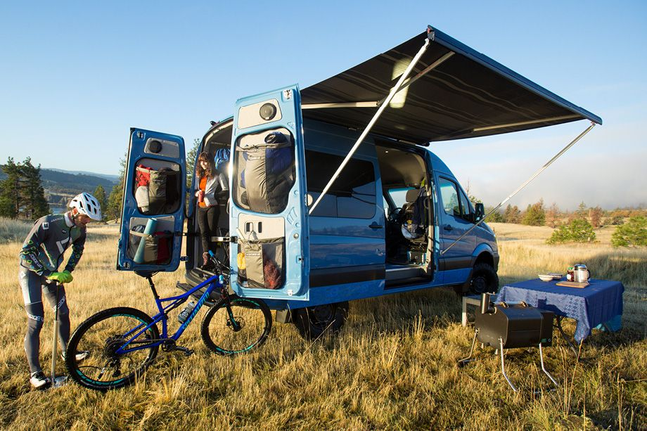A blue can in a clearing with grass. The back doors are open. There are two people next to the back of the van. One person is pumping air into a bicycle tire. There is an open awning on the side of the van.