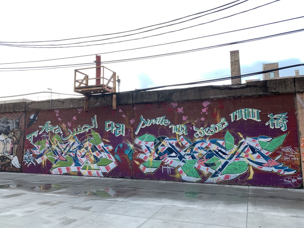 """Using his phone's translator app and his imagination, Lavie Raven turned this stretch of alley wall in Edgewater into a multicultural celebration. The mural includes the word """"bridge"""" in nine languages and the words """"Ahimsa"""" (nonviolence and a respect for all living things) and """"Namaste"""" (a respectful greeting) in graffiti-inspired lettering."""
