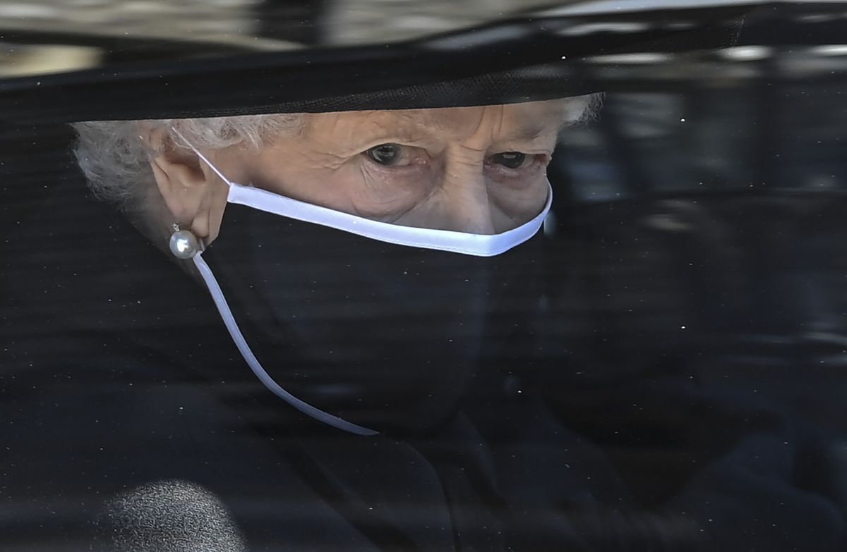 Britain's Queen Elizabeth II follows the coffin in a car as it makes it's way past the Round Tower during the funeral of Britain's Prince Philip inside Windsor Castle in Windsor, England Saturday April 17, 2021.