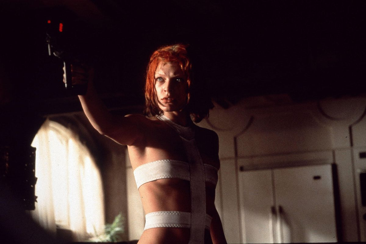 Milla Jovovich in The Fifth Element wearing her white body suit and holding a gun