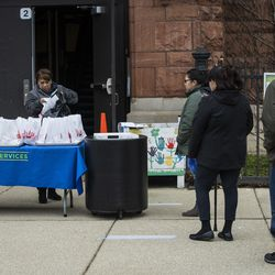 A line of parents wait as Edith Quinones, the lunchroom manager, packs a bag of three days of free breakfast and lunch meals for students at William P. Nixon Elementary School, 2121 N. Keeler Ave., Thursday morning, March 19, 2020. All Illinois schools, including Chicago Public Schools, are closed for weeks amid fears of the coronavirus pandemic.