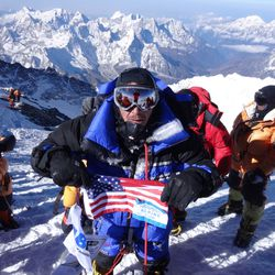 Dave Roskelley stands on the summit of Mount Everest and waves an American flag in 2013.