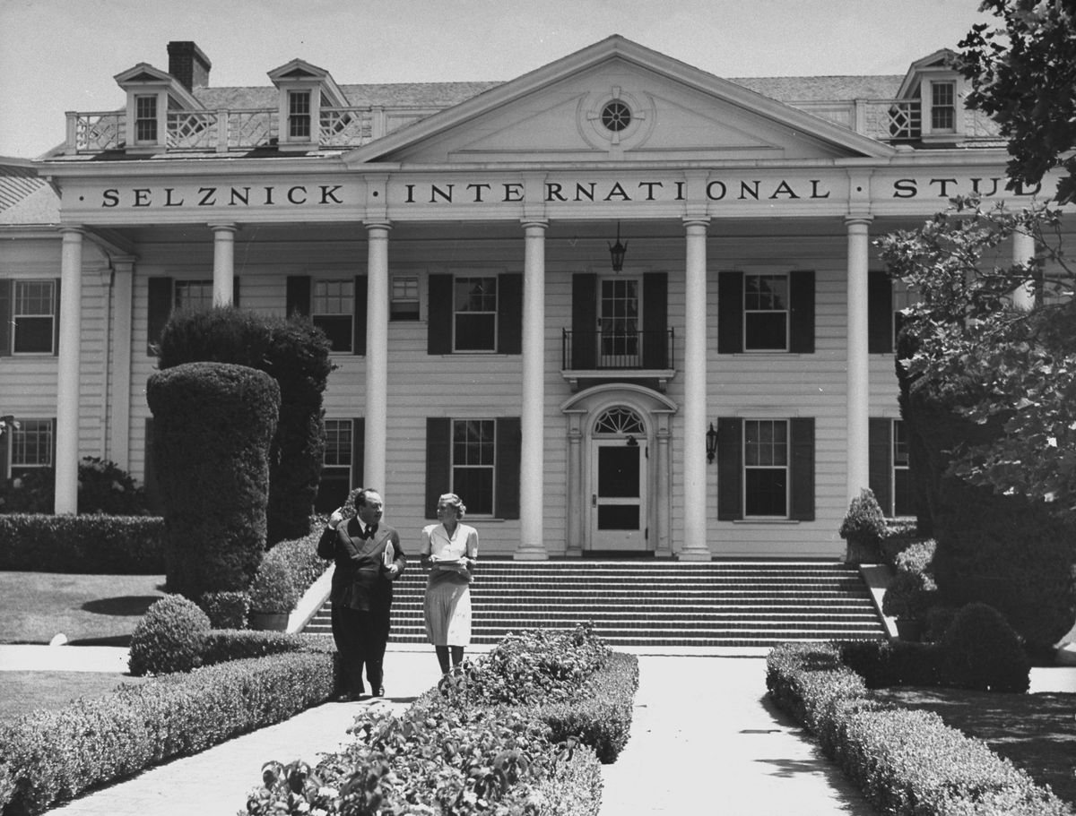 Black and white photo of a short man in a suit walking with a woman in a white sleeveless dress down a concrete walkway lined with manicured shrubs. A mansion with columns and windows is in the background.