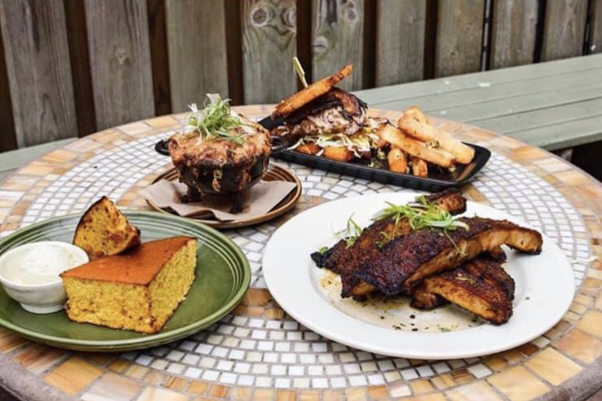 Jerk Shack dishes, including corn bread and ribs, on the outdoor patio