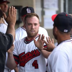 The Salt Lake Bees' Nolan Fontana gets high fives after safely stealing home during a baseball game against the Reno Aces in a baseball game at Smith's Ballpark in Salt Lake City on Monday, June 26, 2017. The Bees wore Trappers jerseys for '80s throwback night.