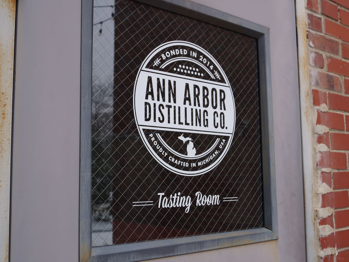 A sign on the window of a metal door for Ann Arbor Distilling Co.