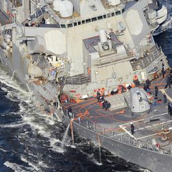 In this Saturday, Junes 17, 2017, photo, the damaged USS Fitzgerald is seen off Yokosuka, near Tokyo, Japan, after the Navy destroyer collided with a merchant ship.  The U.S. Navy says the bodies of sailors who went missing in the collision between the USS Fitzgerald and a container ship have been found aboard the stricken destroyer.