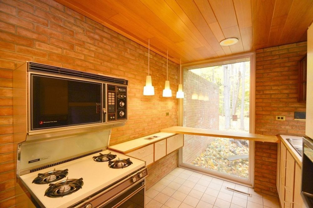 A midcentury modern kitchen with exposed brick walls, white tiled flooring, a stove, and light fixtures.
