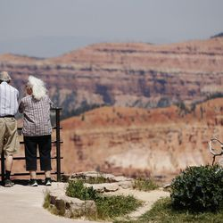 Tourists look over the Cedar Breaks Sunset View overlook as the Brian Head Fire continues to burn in southern Utah on Friday, June 30, 2017. The evacuation order for Brian Head and Dry Lakes was lifted Friday, 13 days after residents were forced from their homes by the raging fire.