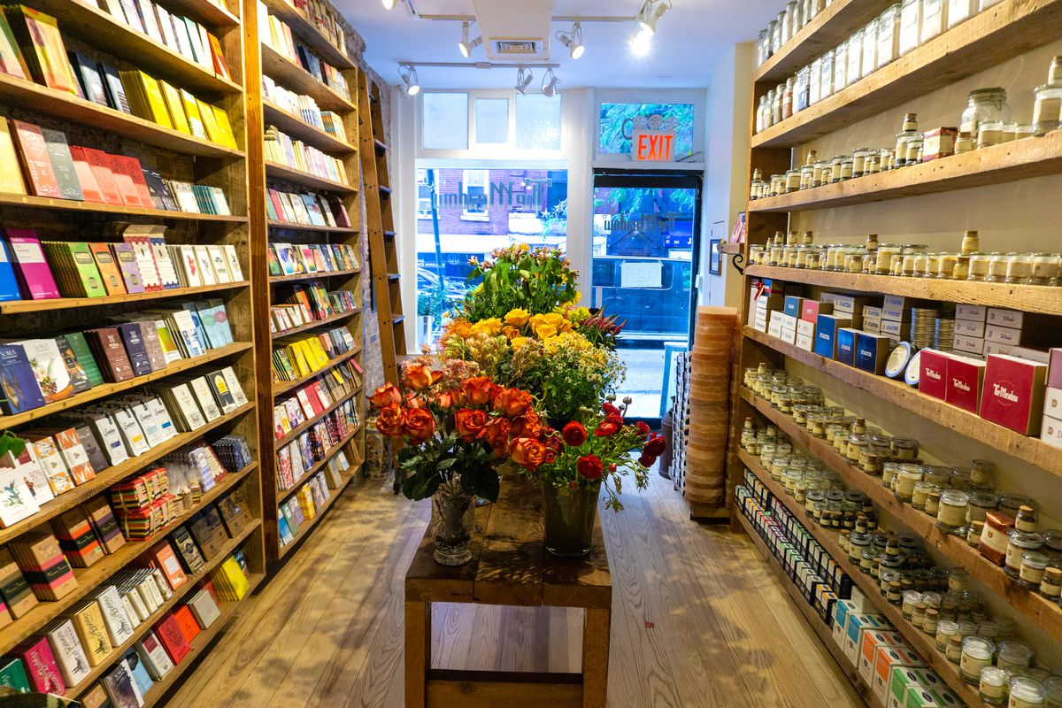An interior shot of a store lined with shelves holding bars of chocolate on one side and jars of salt on the other. A wood table sits in the middle with floral arrangements.