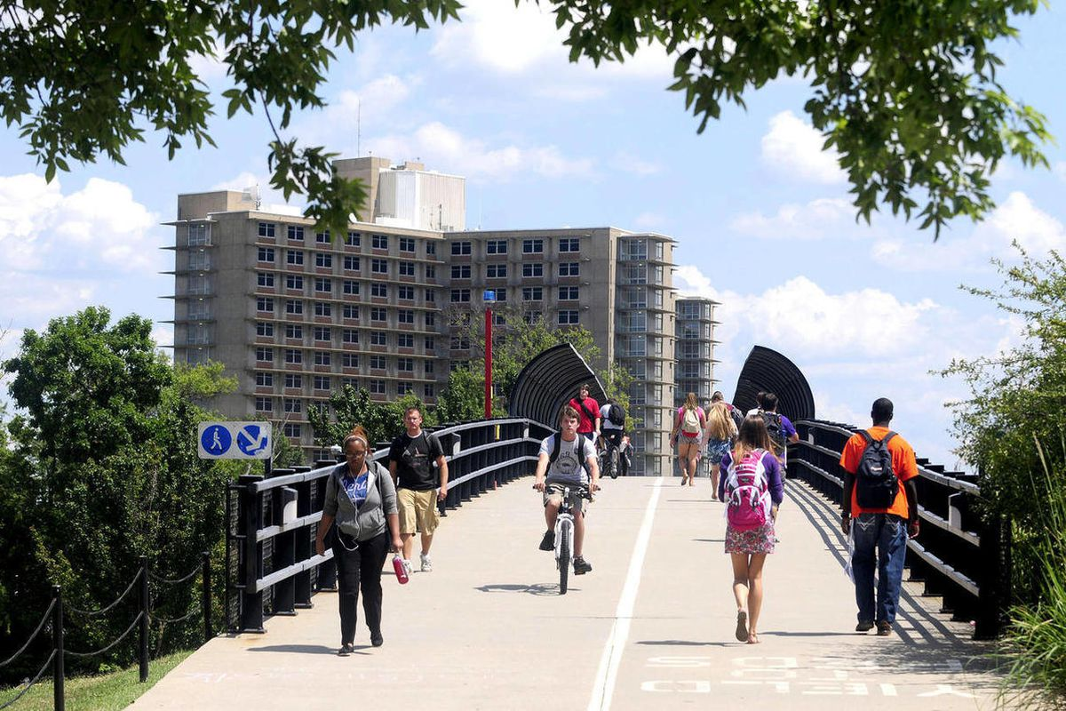 In this Aug. 20, 2012 photo, students walk across a bridge on the first day of classes at Southern Illinois University in Carbondale, Ill. Enrollment at many of Illinois' public universities is down this fall. Administrators at schools such as Eastern Ill