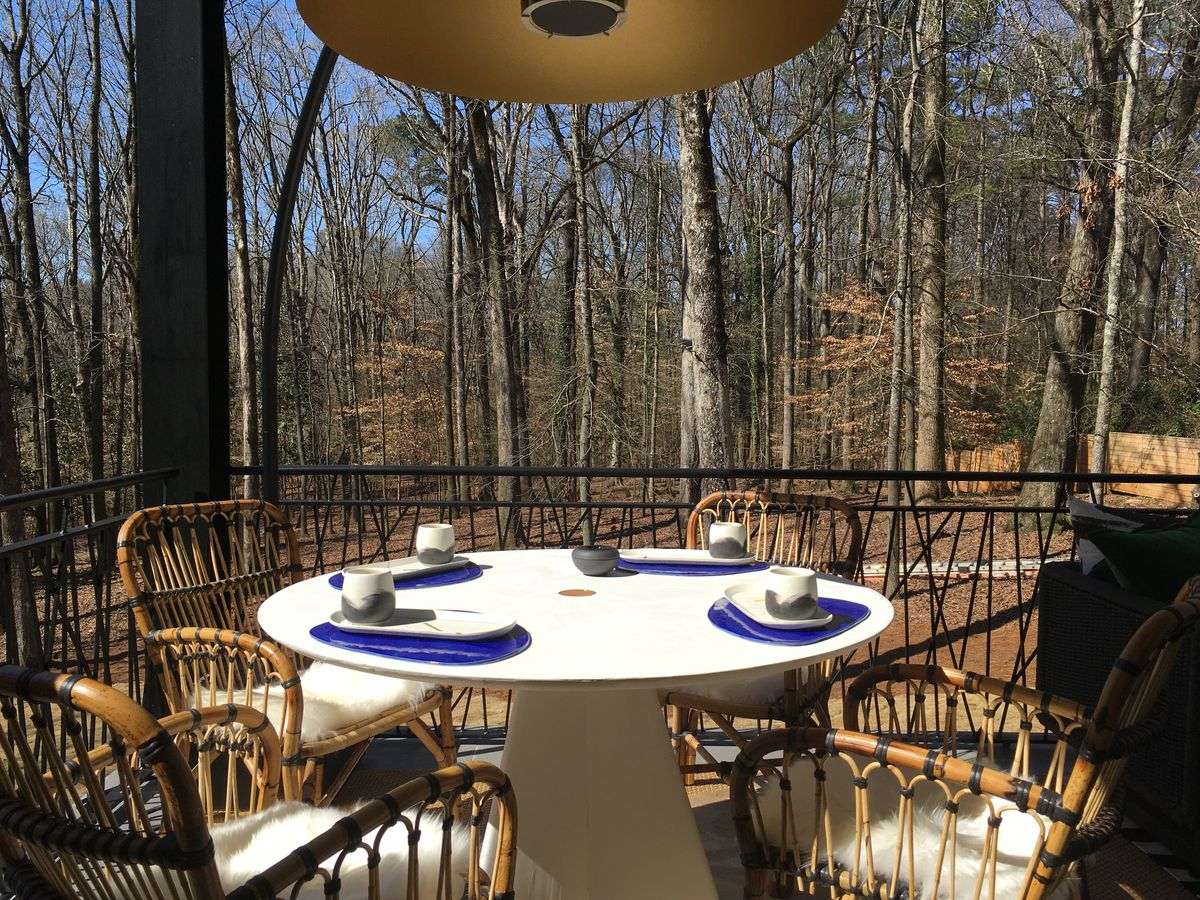 A table with chairs outside near woods for dining.