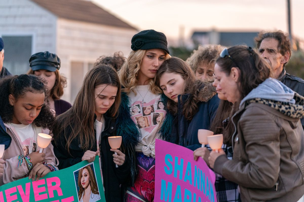 A group of people lean on each other, holding handles and signs for the missing or dead women.