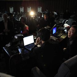 Foreign journalists desperate for news try to get comments from North Korean press center workers, right, in Pyongyang, North Korea, Friday, April 13, 2012. North Korea fired a long-range rocket early Friday, South Korean defense officials said, defying international warnings against a launch widely seen as a provocation