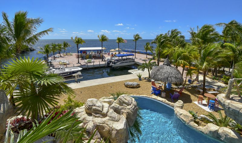 An aerial view looking out at a boat slip with palm trees and a pool.