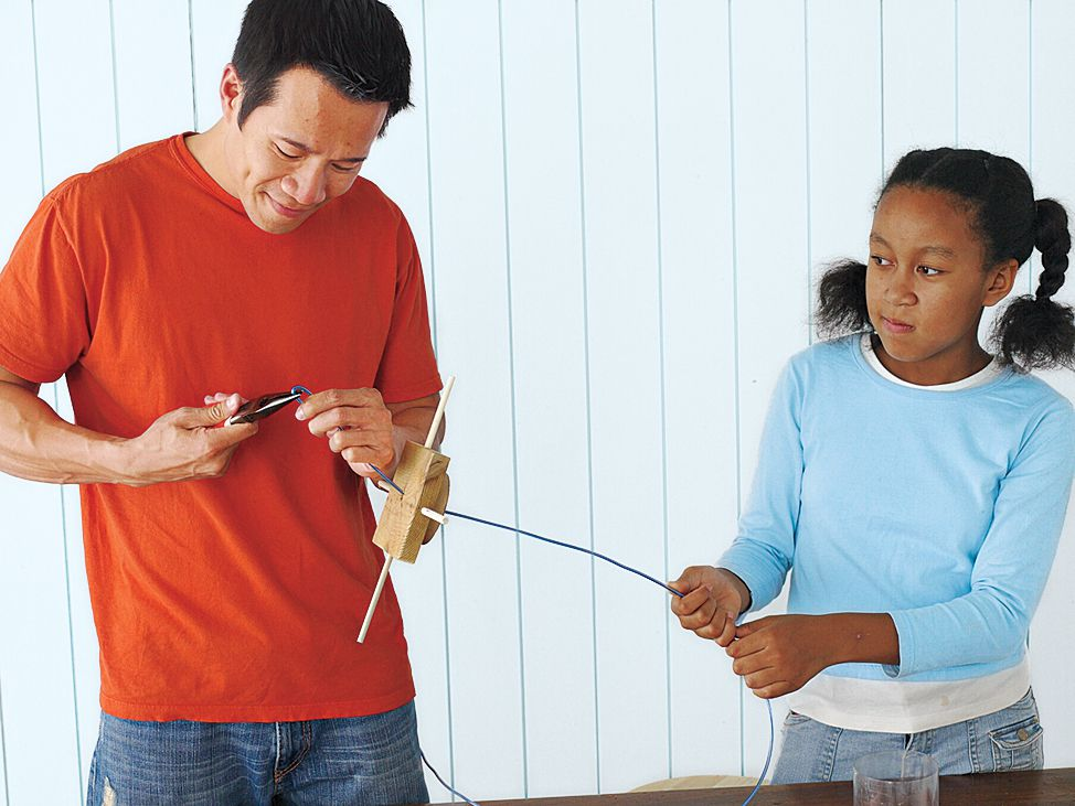 Parent and child wiring the base of the homemade bird feeder.