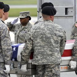 """FILE - In this Wednesday, May 9, 2012 file photo, Air Force Senior Airman Mercedes McCoy-Garrett salutes as an Army carry team places the transfer case containing the remains of Army Pfc. Dustin Gross, 19, of Jeffersonville, Ky., into a transfer vehicle at Dover Air Force Base, Del. Until Gross was killed by an IED on May 7, 2012, most people in the area had matters other than the war on their minds. """"Seems like times are getting harder and I think that's what most people are focused on, just everyday living,"""" his mother, Angie Brown, says. But Gross was just 19 when he died, only a year from the graduation stage at Montgomery County High School, where many people still remembered him as the football team's running back. More than 2,000 people came to his funeral, held in the high school gymnasium and most businesses in Mt. Sterling, including the local Wal-Mart, closed for at least an hour, to pay respect."""