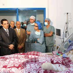 FILE -  In this file photo released Dec. 28, 2010 by the Tunisian Presidency office, Tunisia's President Zine El Abidine Ben Ali, 2nd left, visits Mohamed Bouazizi, a young man who set himself on fire acting out of desperation after police confiscated the fruits and vegetables he sold without a permit, at Ben Arous Burn and Trauma Centre, in Tunis.  For decades, Tunisia has promoted itself as an Arab world success story, a place where the economy is stronger than in neighboring countries, women's rights are respected, unrest is rare and European tourists can take stress-free vacations at beach resorts. But the recent protests have exposed a side of Tunisia that the country has long tried to hide: the poverty of the countryside, poor job prospects for youths and seething resentment at the government of President Zine El Abidine Ben Ali, who has ruled Tunisia with an iron fist since 1987.