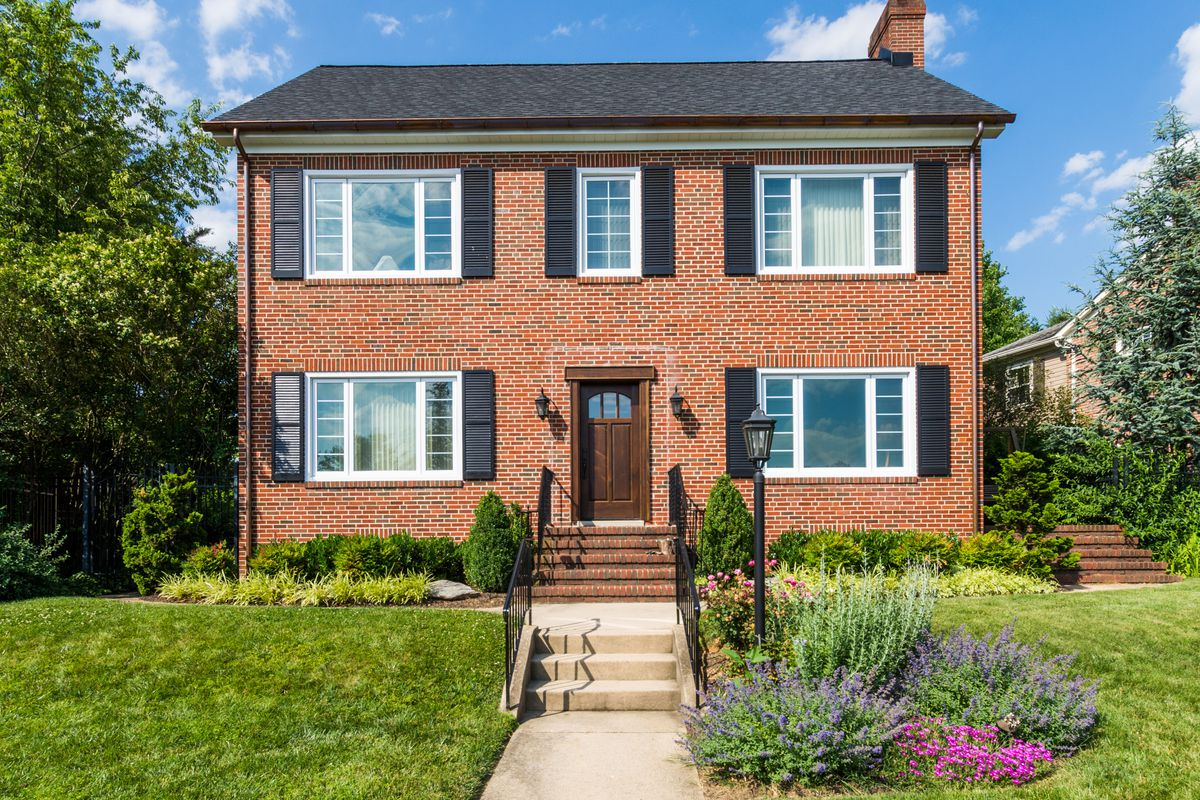 A red brick home in Maryland with black shutters, pink and purple flowers, green front yard, and concrete stairs with black iron railing leading to front door.