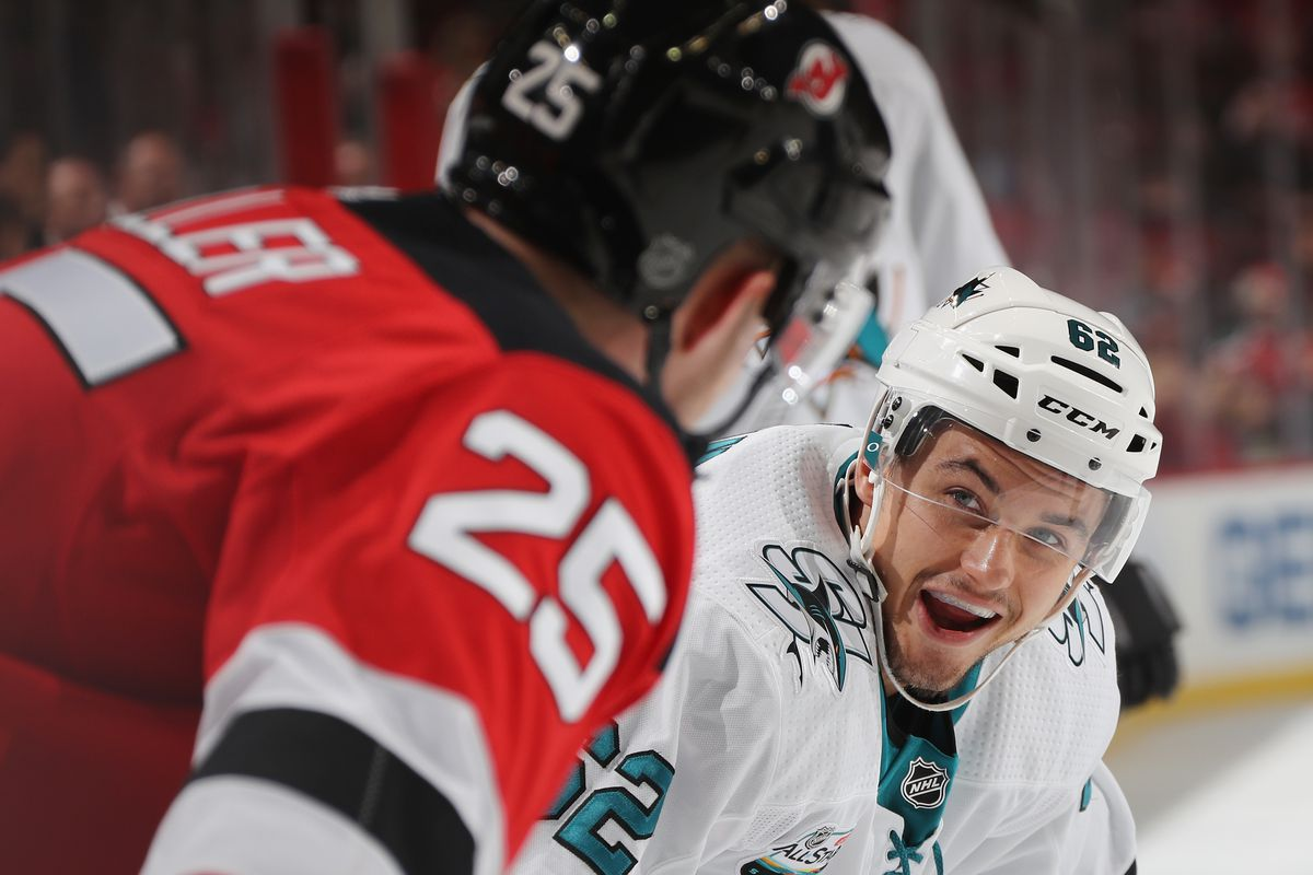 NEWARK, NEW JERSEY - OCTOBER 14: Kevin Labanc #62 of the San Jose Sharks chats with former teammate Mirco Mueller #25 of the New Jersey Devils during the first period at the Prudential Center on October 14, 2018 in Newark, New Jersey.