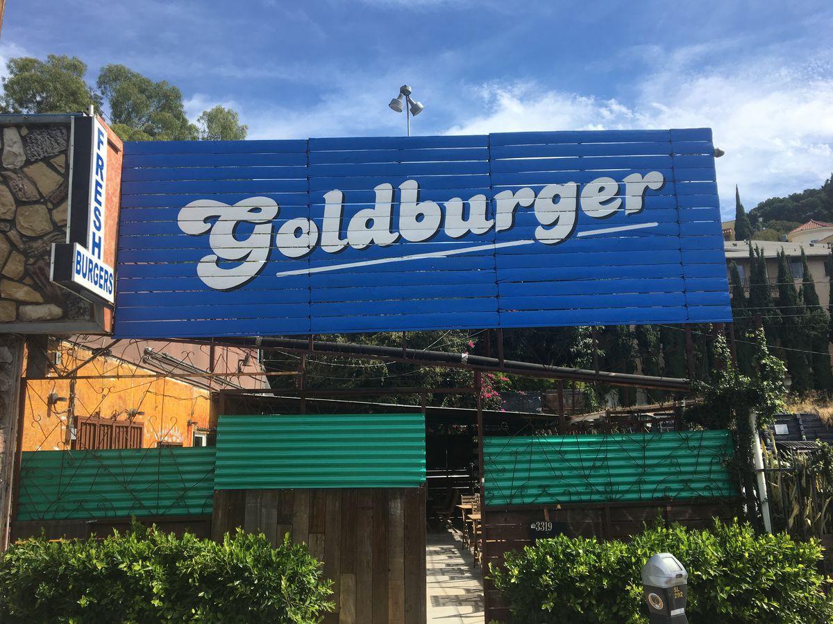 A blue sign reads Goldburger over a restaurant space.