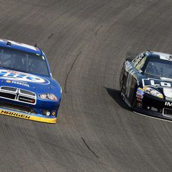 Brad Keselowski, left, leads Jimmie Johnson (48) during the NASCAR Sprint Cup Series auto race at Chicagoland Speedway in Joliet, Ill., Sunday, Sept. 16, 2012.