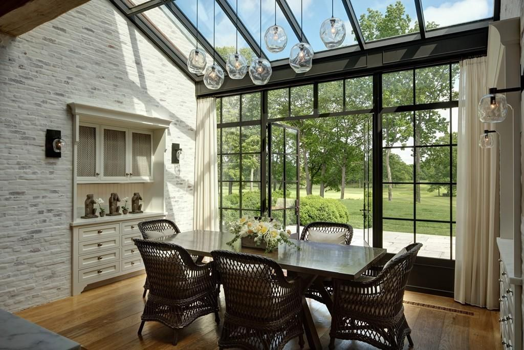 A dining room with a wall of windows, and the windows extend to over part of the ceiling.
