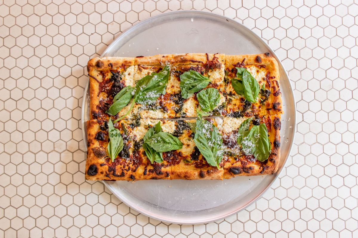 An overhead photograph of a slice of pizza with sprigs of basil and dollops of white cheese