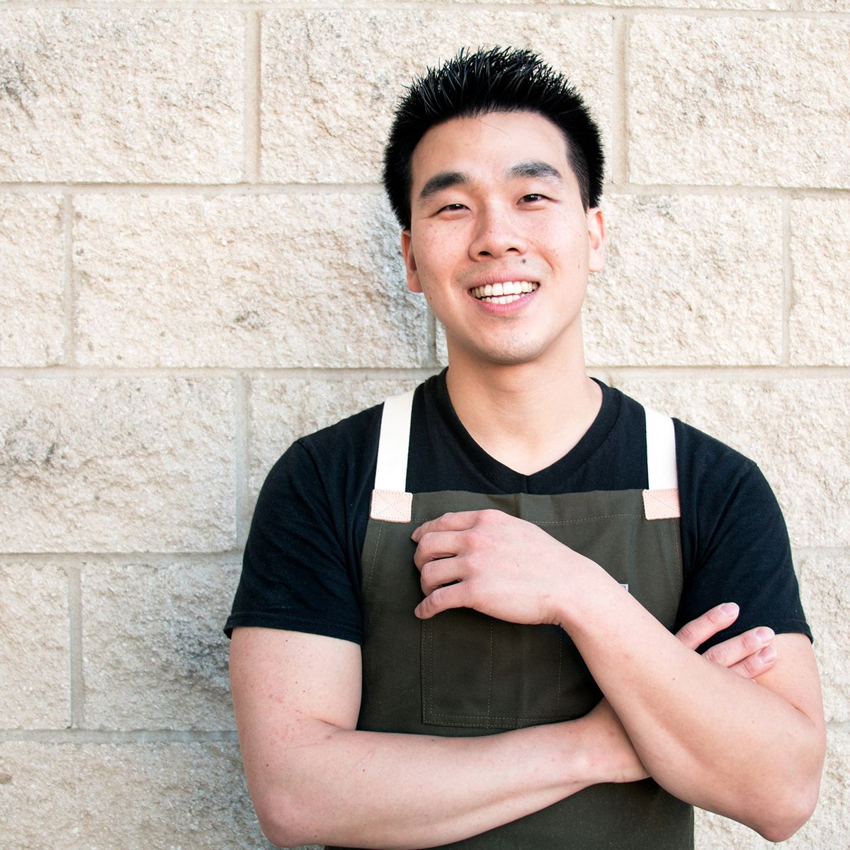 chef Dave Park smiling against a white brick wall