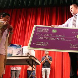Siaosi Heimuli, left, becomes emotional as Garrett Laws, right, presents him with a scholarship check for $1,000 at a ceremony honoring Heimuli as Granite School District's Absolutely Incredible Kid at Granite Park Junior High in Salt Lake City on Monday, May 23, 2016.