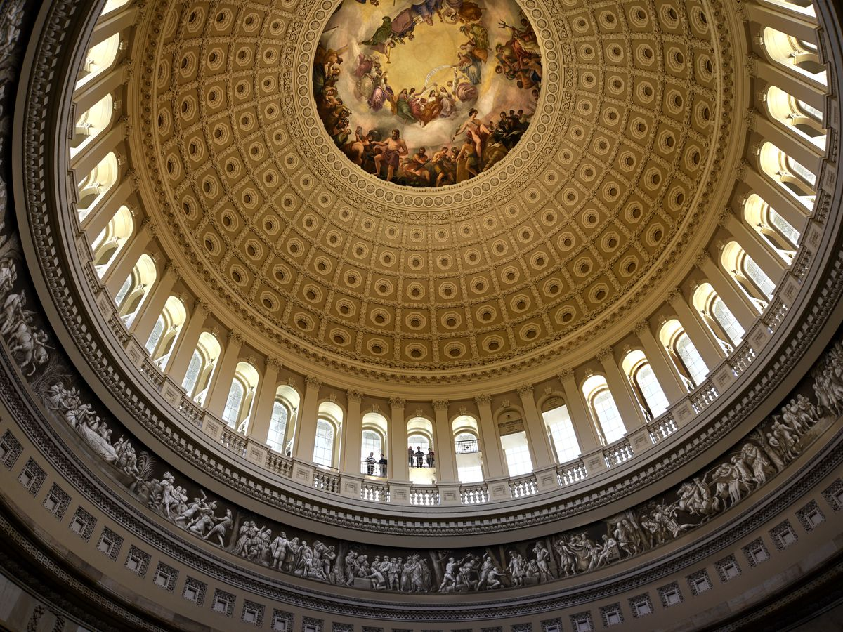 The interior of a dome in a capital building. There is a painted fresco in the middle of the ceiling.