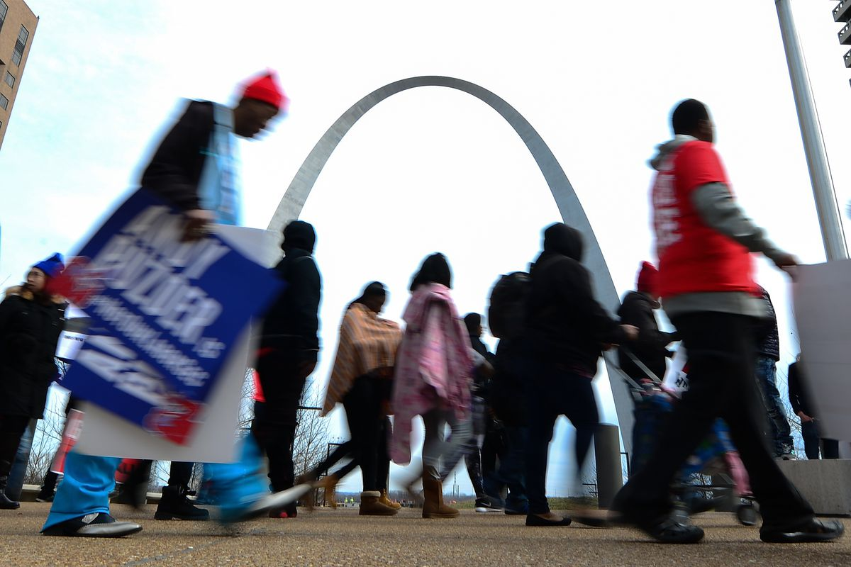 Protesters walk past the Arch during a rally against Labor nominee Andrew Puzder at Hardee's Headquarters on February 13, 2017 in St Louis, Missouri. The protesters feel that Mr. Puzder will not have the best interest of workers in mind due to his record