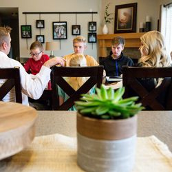 """The Kirby family gathers for a gospel study at home using """"Come, Follow Me — For Individuals and Families: Book of Mormon 2020,"""" a manual for The Church of Jesus Christ of Latter-day Saints, in Lehi on Sunday, March 15, 2020."""