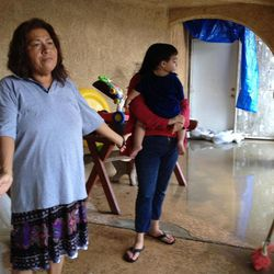 Martha Manangan, left, stands in her flooded home in Mecca, Calif.  after a sudden heavy rain flooded the area early, Tuesday, Sept. 11, 2012.  Early morning thunderstorms over southeastern California's Coachella Valley has caused flooding in mobile home parks in Mecca and Thermal. The National Weather Service says more than 5 inches of rain fell in an area bounded by the Salton Sea communities of Oasis, Mecca and North Shore. More than 3 feet of water flooded Highway 111.