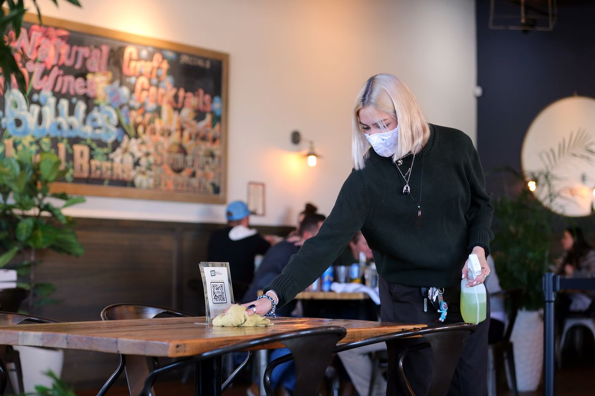 Allie Chernosky cleans a table and chairs at OAK Wood Fire Kitchen in Draper on Tuesday, Dec. 8, 2020.