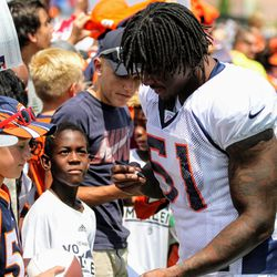 Broncos ILB Todd Davis signs autographs for young fans after the final open practice.