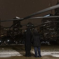 Mayor Lori Lightfoot (left) and first lady Amy Eshleman hold candles while looking toward a darkened Chicago skyline from Millennium Park during a national COVID-19 memorial, Tuesday, Jan. 19, 2021.
