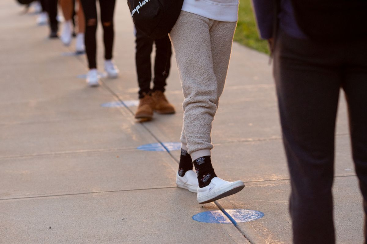 School children in a socially distanced line, only their legs and feet are visible.