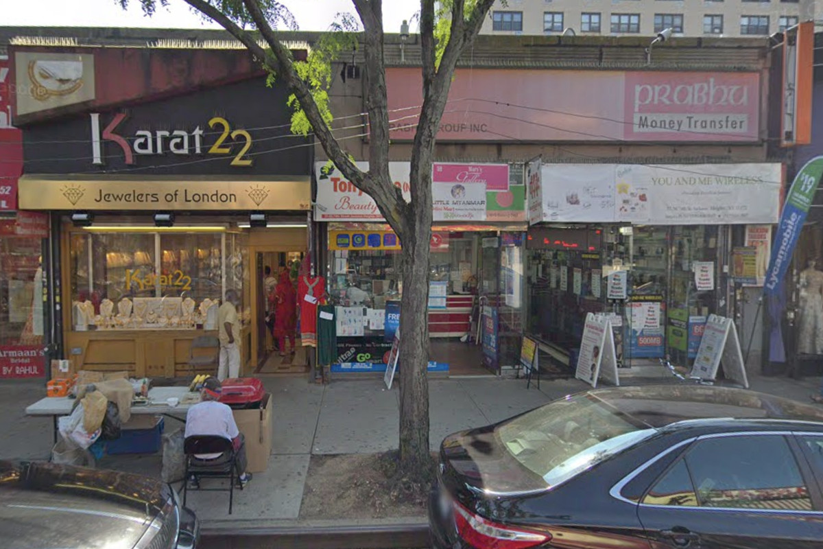 Cars are parked in front of two storefronts in Jackson Heights, which advertise cell phones and other products for sale