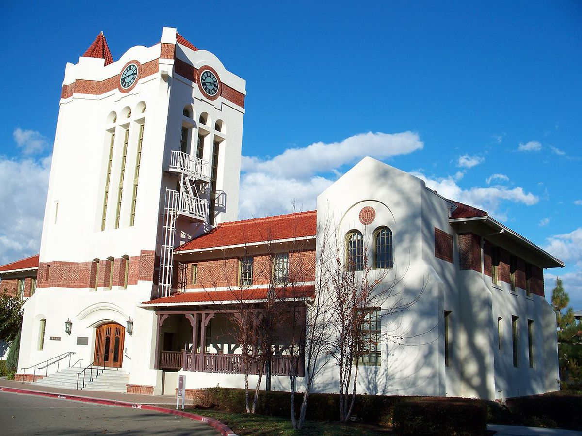 The exterior of Agnews Hospital in California. The facade is white with red decorative detail.