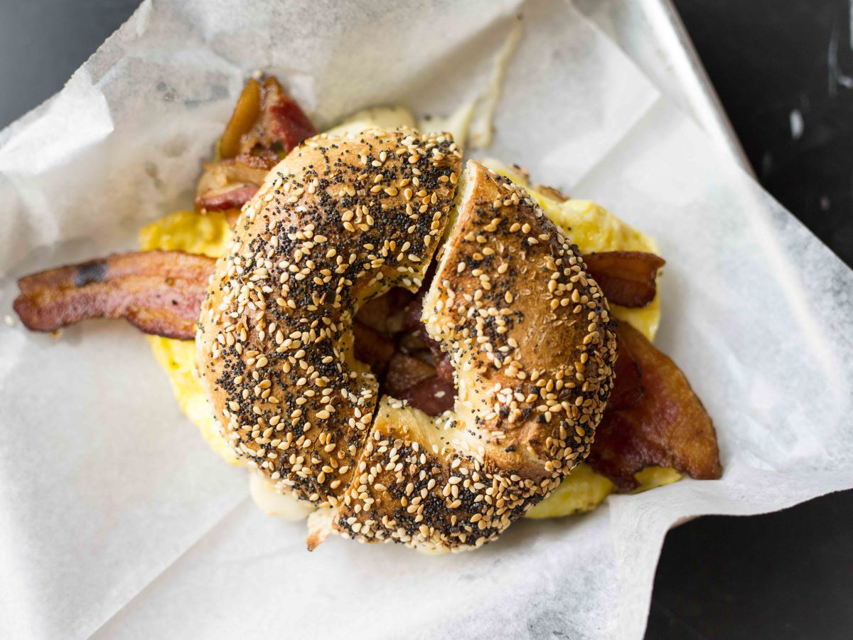 a bagel with bacon and egg on it