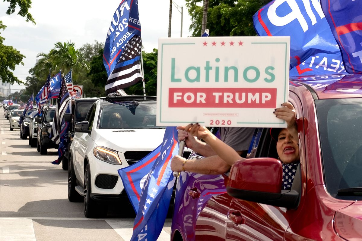 """A person holds a sign reading """"Latinos for Trump"""" out the window of a car."""