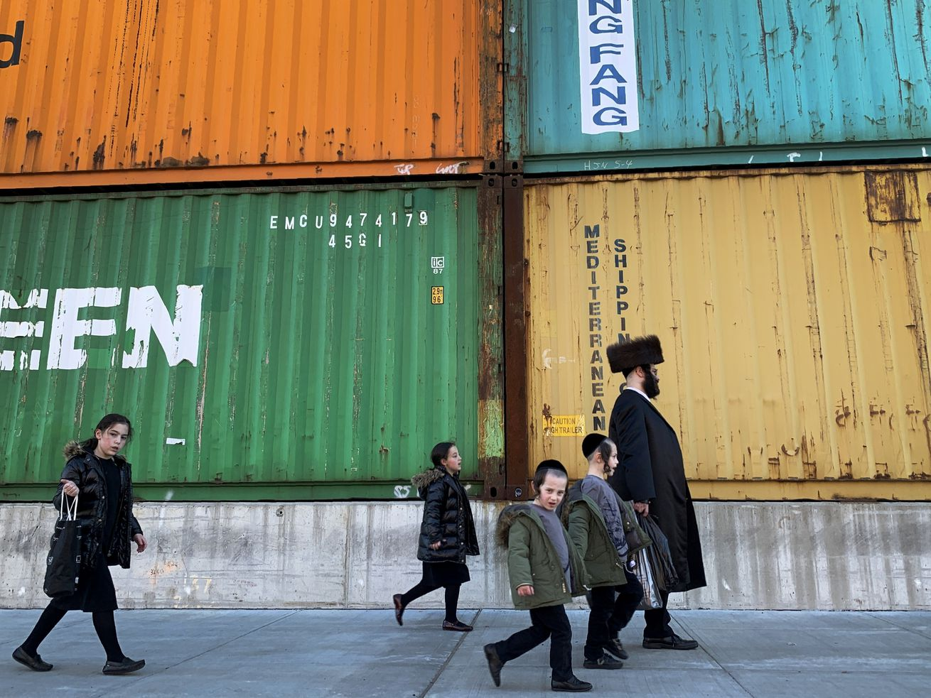 In this Tuesday, March 30, 2021 file photo, members of the Orthodox Jewish community walk past shipping containers in the South Williamsburg neighborhood of Brooklyn, New York.
