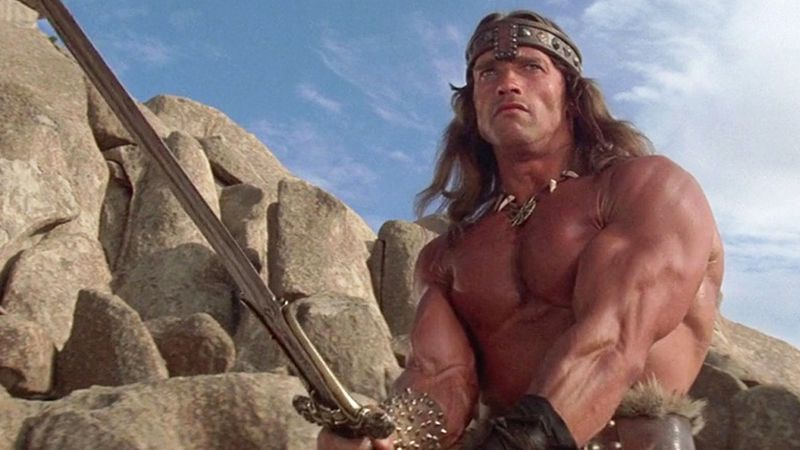 An extremely buff man wields a sword.