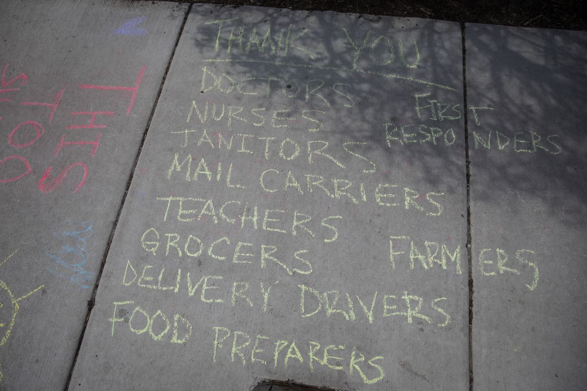 Thank-you messages aimed at first-responders, doctors, nurses, teachers, grocers and others written in chalk on a sidewalk outside a home on South Loomis Street near West Harrison Street in Little Italy.